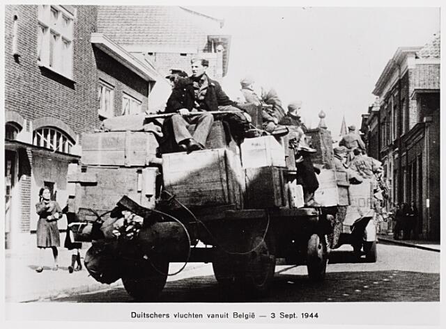 013171 - Tweede Wereldoorlog. Duitse militairen rijden door de Kerkstraat naar de Markt en vandaar naar het noorden. Op de voorste vrachtwagen staan de letters THOR, waaruit blijkt dat deze vrachtwagen gevorderd is van de THOR-bode diensten.
