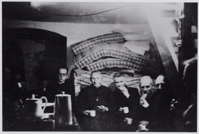 045675 - WO2 ; WOII ; Tweede Wereldoorlog. Schuilkelder in de pastorie van de parochie St. Jan Onthoofding aan de Kerkstraat gedurende de gevechtshandelingen in oktober 1944. Derde van links pastoor Van Riel. De anderen zijn paters van de congregatie van de H. Familie (Nieuwkerk).