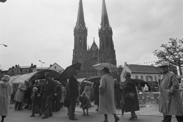TLB023000120_001 - Belangstellenden voor militaire tenten uit de 2e Wereldoorlog tijdens een manifestatie ter gelegenheid van de Bevrijdingsfeesten in 1989.  Op de achtergrond de Heuvelse Kerk met bijbehorende Pastorie