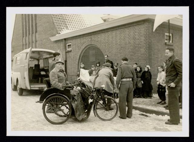 1696110 - Het Nederlandse Rode Kruis afdeling Tilburg. Op tweede kerstdag 1950 organiseert de transportcolonne voor de tweede keer een kerstfeest voor de bedlegerige zieken en invaliden. Dit jaar is de kerstviering in het parochiehuis aan de Wassenaerlaan. Een gast op brancard wordt uit de ambulance van het Rode Kruis getild. Op de voorgrond een man in een speciale rolstoel fiets die kan worden aangedreven met de hand.
