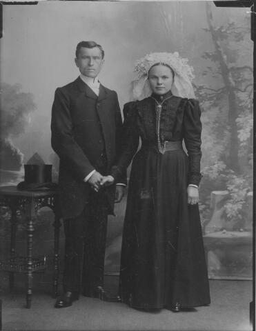 063978 - Trouwfoto van klompenmaker Johannes Cornelis van Berkel en Maria Neggers. De bruid draagt een tule muts, afgezet met Parijse kloskant en daarop  een poffer die alleen uit kunstbloemen bestaat met aan de zijkanten korte staartlinten.