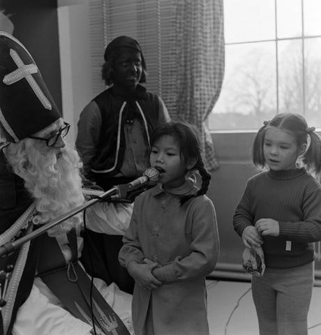 1237_004_104-1_006 - Sinterklaas. Tijdens een Sinterklaasviering bij wolfabriek 3 Suisses praat Sinterklaas met twee meisjes. Zwarte Piet kijkt toe.