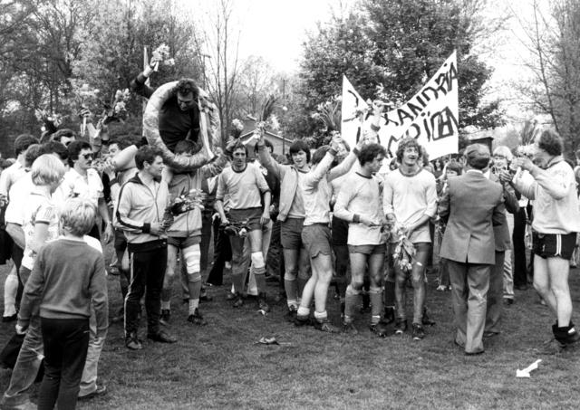800062 - Voetbalvereniging Taxandria. Voetbal. Kampioen.  Links met zonnebril Helmus Damen, bij spandoek met bloemen Mart vd Biggelaar, op schouders met krans Mels Dielen.