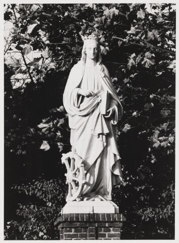 067875 - De H. CATHARINA VAN ALEXANDRIË behoorde tot de meest populaire heiligen van de middeleeuwen. Zij stierf de marteldood in 307. In de christelijke kunst is het rad waarmee zij geradbraakt werd, haar vaste attribuut. In 1903 was dit beeld het laatste dat aan de beeldengalerij van het kerkhof Bredaseweg werd toegevoegd. Het werd geschonken door J. Castelijn, wiens vrouw ook Catharina heette.   Trefwoorden: Kunst, openbare ruimte.