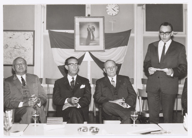 037758 - Textielindustrie. Toespraak door Frans Enneking jr. met links van hem Frans Enneking sr., burgemeester mr. Cees J. G. Becht (1910 - 1982) en Hein Enneking sr.