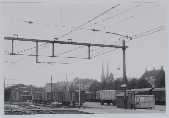 037106 - Spoorwegen, Goederenemplacement, N.S.: Los- en laadplaats aan de Spoorlaan met op de achtergrond de Heuvelse kerk in 1959.