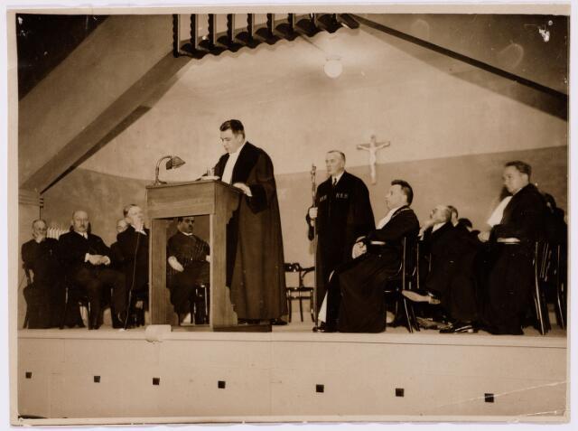 051937 - Hoger Voortgezet Onderwijs. R.K. Handelshogeschool te Tilburg.  Tijdens de inaugurale rede van ir.dr. Gelissen als hoogleeraar aan de R.K. Handelshogeschool te Tilburg. Naast de redenaar zittend prof. dr. Weve, rector magnificus van de R.K. Handelshogeschool.