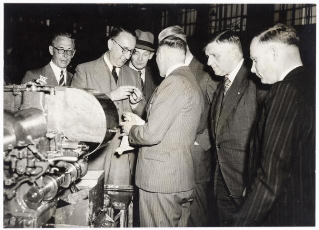 038667 - Volt. Zuid. Bezoek van burgemeester en wethouders van Tilburg aan Volt op 26 april 1949. Waarschijnlijk bekijkt men hier een z.g.n. revolver- of een automatendraaibank, althans het product wat eruit komt. V.l.n.r.: Dhr.de Vleeschouwer bedr. leider, burgemeester van Voorst tot Voorst, Ir.Kipperman directeur, met streepjes kostuum Dhr.Onrust afd. chef fabricage- of productie-afdeling Metaalwaren, WethouderJanssens en Ir. Vroom bedrijfsingenieur van Volt.