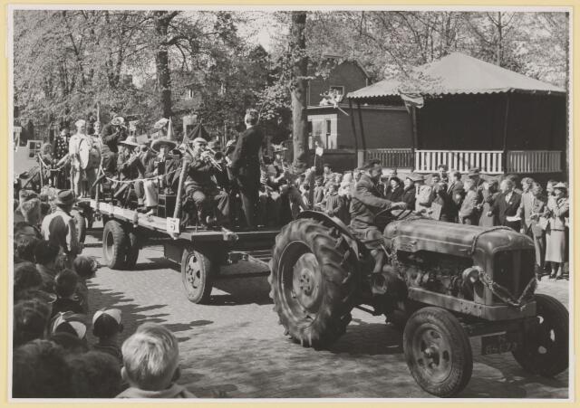 """080794 - 10 jaar bevrijding. 1945-1955. no.5. R.K.Harmonie """"St. Cecilia"""". Veel toeschouwers met links vooraan drie welpen. Man met hoed en sigaar."""