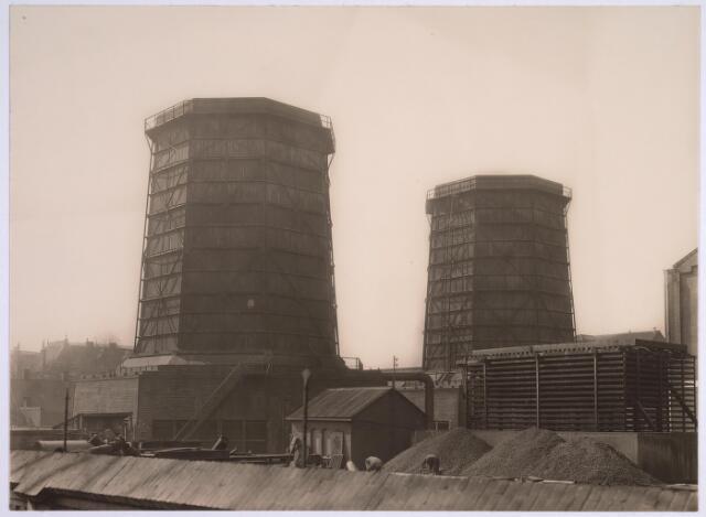 025155 - Energievoorziening. Houten koeltorens en kolenopslag op het terrein van de gasfabriek aan de Lange Nieuwstraat. De rechter koeltoren werd op 10 april 1929, tien jaar na de eerste, in gebruik genomen.