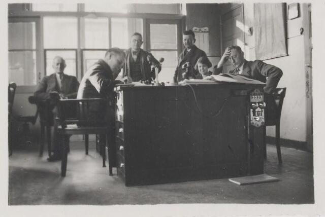 081247 - Gemeentepersoneel in het raadhuis aan de Nieuwstraat. V.l.n.r.: Jan Klaassen bode, Bart van Hezewijk, Louis Smeulders, Jan Kamp, Riet vd Wildenberg en Janus Hoevenaars secretaris.