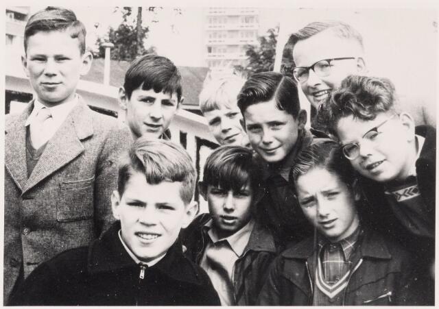 051185 - Leerlingen van de zesde klas van de katholieke lagere school voor jongens Don Bosco. Ze zijn hier op schoolreis naar of in Rotterdam, in juli 1956. Ze staan klaar om aan boord te gaan van de rondvaartboot Spido. De Don Boscoschool, destijds gevestigd aan de Spoordijk,  hoorde bij de Sacramentsparochie, wijk Armhoefse Akkers. Ze was ontstaan als afsplitsing van de St. Jozefschool op De Heuvel en fuseerde later met de St. Lidwinaschool. Bovenste rij v.l.n.r.: Tom Wiersma, NN, Paul Ebeling, Walther Jansen en met bril Harrie Oldenkotte, die later een eigen makelaars- en assurantiekantoor zou runnen. Verdere namen: Van Antwerpen, Van der Putten, Van Diessen
