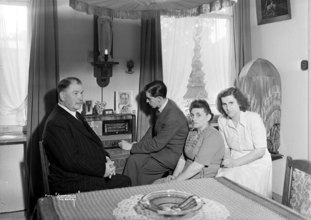 650557 - Schmidlin. De huiskamer in de opzichterwoning van weverij en chemische wasserij de Regenboog. Dit pand lag een de Bredaseweg 213, destijds bewoond door de familie Cools-van Opheusden. V.l.n.r. Vader Toon Cools, zoon Jos, moeder Mientje en dochter Anneke.