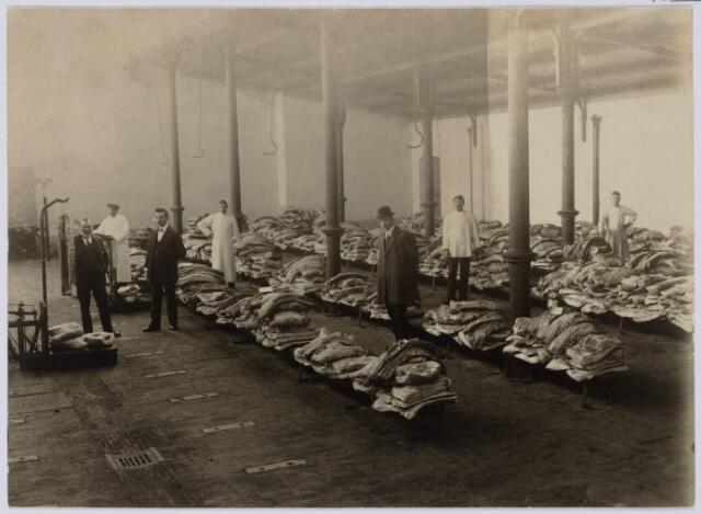 102029 - Vleesdistributie tijdens de Eerste Wereldoorlog. De foto werd genomen in de boterhal naast het gemeentehuis.Van links naar rechts Van Dusseldorp, directeur van de distributiedienst, keurmeester Teijssen, distributie-ambtenaar Van de Schoot, slager Melis, dr. G.L.J. Gooren (met bolhoed) directeur van de keuringsdienst, en de slagers E. Smolders en L. Donders.