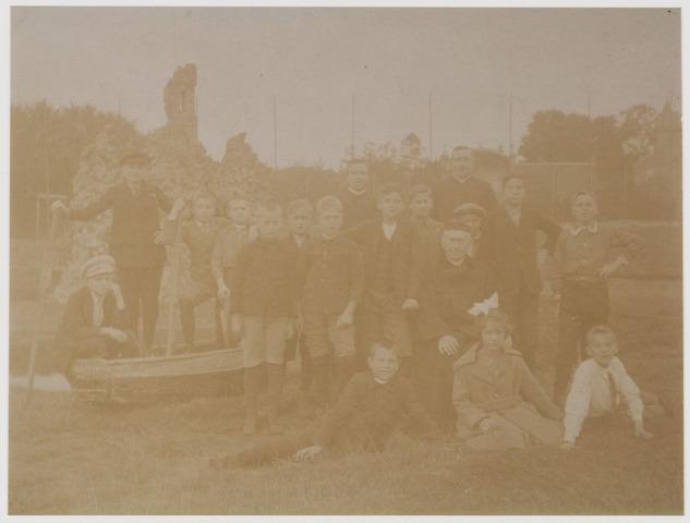 078551 - Twee of drie geestelijken met een groep kinderen met slechts een meisje voor een sloot met roeiboot en man met roeispaan. nn