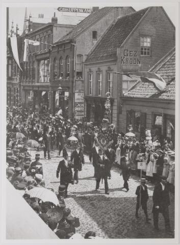 042625 - Optocht in de Heuvelstraat omstreeks 1910. Gezien de vlaggen aan de gevels zou het verband kunnen houden met de verjaardag van een lid van het Koninklijk Huis of ter gelegenheid van een tentoonstelling.
