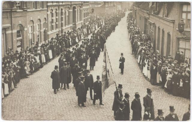 027204 - Op 9 november 1910 werd pastoor mgr.dr. George Willem Joseph Marie van Zinnicq Bergmann in Tilburg begraven. Hij overleed te 's-Hertogenbosch op 6 november 1910. In Tilburg was hij pastoor van de parochie H. Hart (Noordhoek). Hij was ook geheim kamerheer van paus Pius X. De foto werd genomen in de Noordstraat en gaat rechts via de Industriestraat naar de Noordhoekse kerk. Volgens de krant stond 'langs den geheelen weg waar de met rouw omfloersde lantaarns brandden een dichte menschenhaag de stoet eerbiedig gade te slaan onder de droevige tonen van harmonie Excelsior en het muziekkorps van de firma Kessels'. In de kerk werd de requiemmis van Perosi uitgevoerd. Daarna hield mgr. Bots de lijkrede. In de stoet liep ieder groep achter een bordje met nummer. Rechts vooraan met vlag zien we groep 12: het bestuur van de R.K. Gildenbond, vervolgens groep 13: een deputatie van de Katholieke Sociale Actie en groep 14 de leden van het parochieel kerkkoor.