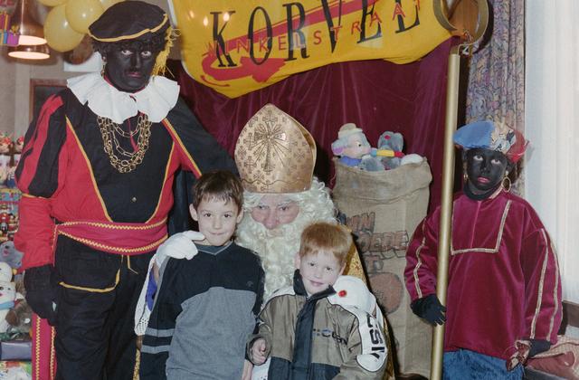 1237_001_003_001 - Feest. Korvel Winkelstraat. Sint Nicolaasviering. Twee kinderen poseren met Sinterklaas en twee Zwarte Pieten tijdens een Sinterklaasfeest georganiseerd door winkeliersvereniging Korvel Vooruit.