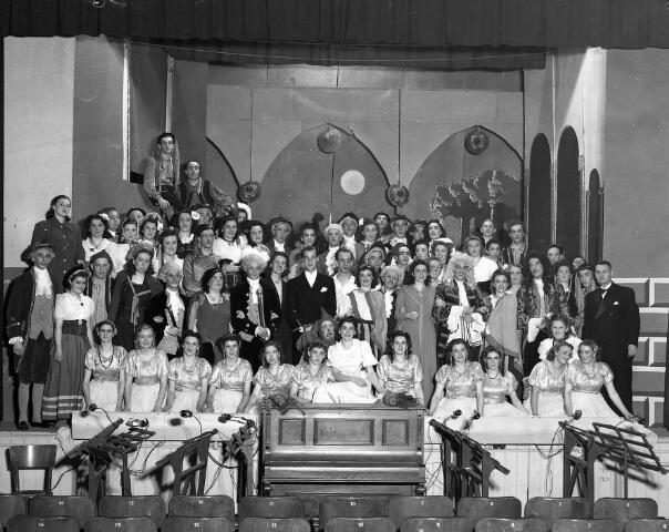 """650491 - Groepsfoto. Het Tilburgs Gemengd Koor, november 1948. Operette """"Eine Nacht in Venedig"""". In het midden, met zwart colbert en wit pochet, dirigent Cees van Gorp."""