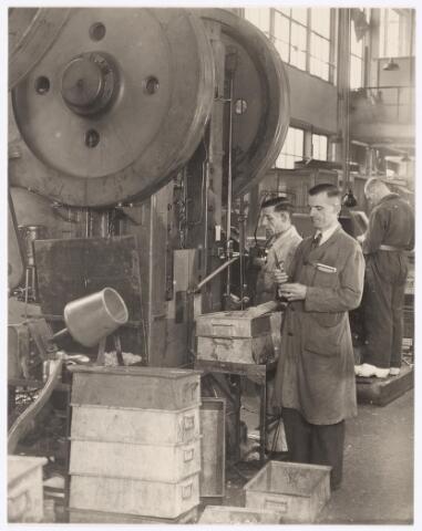039021 - Volt. Zuid. Productie of fabricage  van onderdelen in afd. metaalwaren. Dhr. L.C.C. Louer was steekproefcontroleur in die afdeling in gebouw M zuidzijde. Deze foto van hem, met grijze stofjas, is gemaakt t.g.v. zijn 25 jarig dienstjubileum in 1947. Hij controleert hier een product afkomstig van de grote excenterpers naast hem. Voltstraat heette toen Nieuwe Goirleseweg.