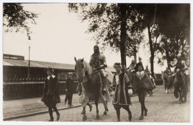 048923 - optocht op 18 augustus 1923 t.g.v. het 25-jarig kroningsfeest van koningin Wilhelmina. De grote historische optocht telde honderden deelnemers die vertrokken vanaf de Kromhoutkazerne aan de Bredaseweg, waar 1e luitenant Momma de leiding had. De kleding voor de stoet werd geleverd door de firma Janssen & Bierens (de Regenboog), de kleding werd gemaakt door de zusters Ursulinen en de Vliegkappen. De heer Kessels componeerde twee feestmarsen:  'Holland jubelt' en 'Neerland en Oranje'. De verschilende groepen waren eerder geschilderd door Jan van Delft. de schilderijen werden tentoon gesteld in verschillende etalages in de Heuvelstraat (rubriek weerzien). Hier trekt de stoet door de Spoorlaan