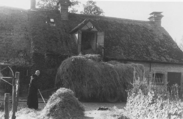 105256 - Monnikenwerk Broeder Vermeulen bezig met het verwerken van hooi bij de varkensstallen van de abdij, in 1938. Kloosters Kloosters. Sint Paulusabdij.