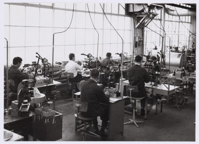 038971 - Volt. Noord.Productie of fabricage afd. Deflectieunits.Vermoedelijke plaats hal NA ca. 1965. Hier het wikkelen van Beeld- en Lijnspoelen wat toen nog een voor een gebeurde. Op de voorgrond links een handmatig bakapparaat voor de lijnspoel. Later is dit werk geautomatiseerd en rolde elke 16 seconden een compleet gewikkelde en gebakken lijnspoel of beeldspoel uit de wikkelautomaat.