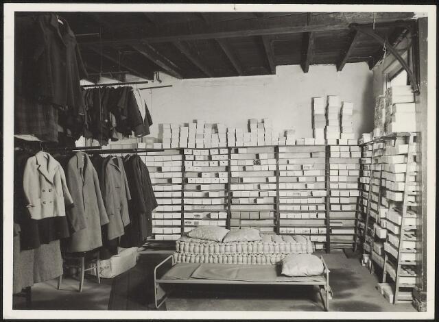 603914 - Vincentius vereniging, Tilburg.  Onder de goederen die in 1958 met 48 vrachtwagens aangevoerd werden,  bevonden zich ook nogal wat dozen met schoenen. In het Centraal Magazijn werden die netjes gesorteerd en overzichtelijk opgestapeld. Aan de linkerkant hangen de korte jasjes en mantels klaar. Er werd blijkbaar niet alleen kleding aangevoerd. In het midden is ruimte voor een bed met een kussen en erachter liggen 2 matrassen en 2 kussen. Ook die werden gegeven aan hen die dat nodig hadden.