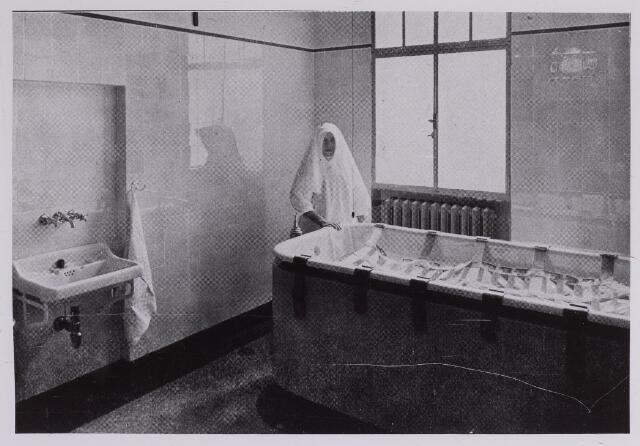 """041679 - Elisabethziekenhuis. Gezondheidszorg. Ziekenhuizen. Badkamer met verpleegster St. Elisabethziekenhuis.Het gaat hier om een z.g. """"permanent"""" bad. """"De permanente baden kunnen soms gedurende weken en maanden gebruikt worden en geven dan goede resultaten. Bij ernstig ruggemergslijden met decubitus worden zij toegepast om den druk op de huid te verminderen en de reinheid der wond te bevorderen. Bij patiënten met sterken graad van waterzucht, met reumatische van spieren en gewrichten en bij verschillende vormen van huidziekte worden zij dikwijls gebruikt. Groote beteekenis hebben zij echter vooral bij de behandeling van onrustige krankzinnigen."""""""