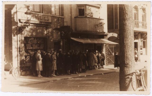 013960 - Tweede Wereldoorlog. Distributie. Wachtende mensen voor de viswinkel van Van Tecklenburg op de Heuvel eind 1944