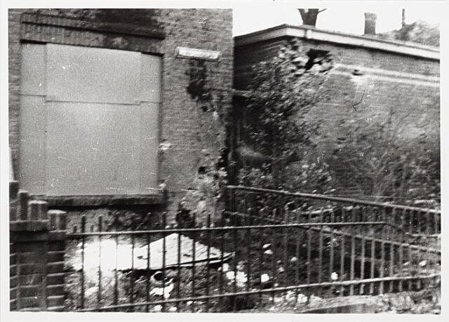 012402 - Tweede Wereldoorlog. Vernielingen. Door granaatinslagen beschadigde woning op het Molenbochtplein. Het eveneens getroffen pand rechts maakte deel uit van de fratersschool