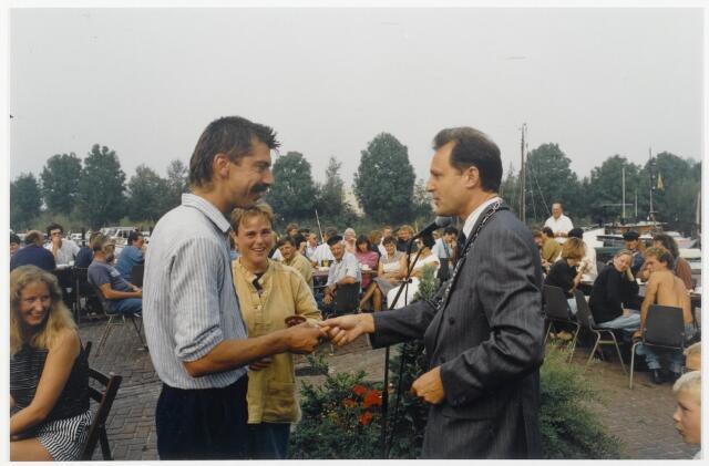 91332 - Terheijden, Zomerfestival 1990. Burgemeester Hans (J) van Brummen (1989 - 1997 - PvdA). de man met de ambtsketen, reikt een prijs uit aan een van de deelnemers tijdens de middeleeuwse festiviteiten.