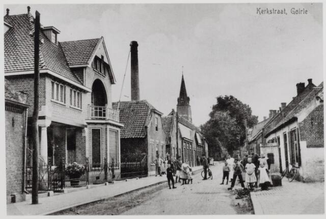 """046350 - De Kerkstraat met links het pand Kerkstraat 25, nu nr. 37,  gebouwd in 1915 voor gemeentesecretaris A. van Vugt. De architect was Jos Donders uit Tilburg. Later woonde in dit pand de weduwe Cato Mutsaers-van Hooff, Wim de Kort, later burgemeester van Ulvenhout en fractievoorzitter van de KVP, en textielfabrikant Jan Mes. Links van dit pand stond een rijtje, inmiddels gesloopte, arbeiderswoningen. Rechts het pand Kerkstraat 23, later huisnummer 35, gebouwd in 1869 door Peter van de Pol. Hier woonden koster Van de Pol en diens zoon, bakker Janus van de Pol. Rechts een dorpspomp. De vrouw voor die pomp is Adriana (Jaoneke) van Erven. Links van de pomp in het wit, haar tweede man, slager Toon Cunen. In 1985 werd door de gemeentelijke monumentencommissie voorgesteld aan B. & W. om een groot aantal panden in de Kerkstraat op de gemeentelijke lijst te plaatsen. Van de straatwand links bleven daarna alleen de eerste drie panden staan. De verderop gelegen textielfabriek van de fa. W. van Enschot & Zonen werd gesloopt om plaats te maken voor de Hoogendries en nieuwbouw. Het huis links van de pomp was een zeer groot en zeer oud wevershuis. In de 20e eeuw was het woonhuis en slagerij, eerst van Kees van Erven-van Erven, later van Toon Cunen, die trouwde met de weduwe van Kees. De laatste bewoner was slager Toontje Appels. Op advies van de inspecteur Volksgezondheid werd het pand in 1949 onbewoonbaar verklaard: """"versleten en uitgeleefd"""". Het pand werd verkocht aan de gemeente en gesloopt. Ter plaatse werd nog in 1949 begonnen met de bouw van twee woningen, ontworpen door architect A. van Gool (laagbouw met dakkapellen, later uitgebreid met een derde woning)."""