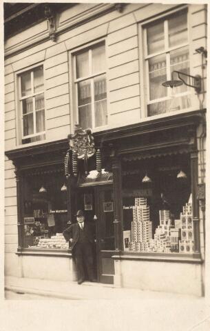 021757 - Tabakswinkel van Frans Woestenbergh omstreeks 1915. In 1912 verwierf de zaak het predikaat hofleverancier. In de deuropening staat zoon Sjef. Later kwam in het pand de modezaak Mutsaers - van Thillo