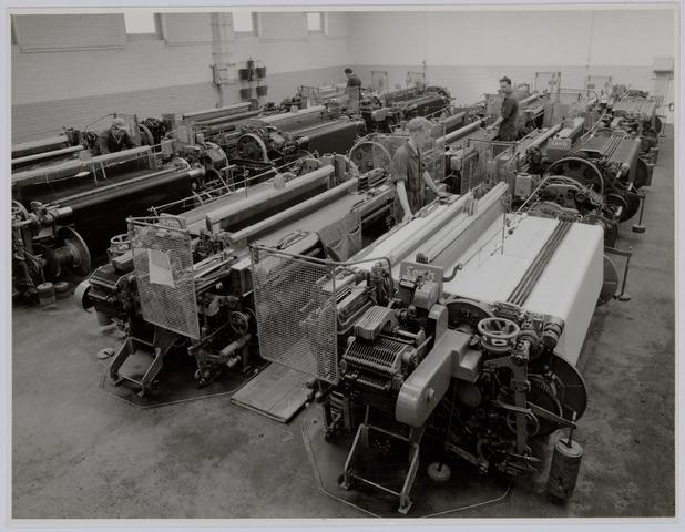 037479 - Textiel. Weefmachines zonder bovenbouw. De dolby, het mechanisme dat de schaften beweegt, is hier naar de zijkant van het getouw verplaatst (rechts op de voorgrond). Het hekwerk ernaast is de spoelenvanger, bedoeld om een uit de bocht gevlogen schietspoel op te vangen