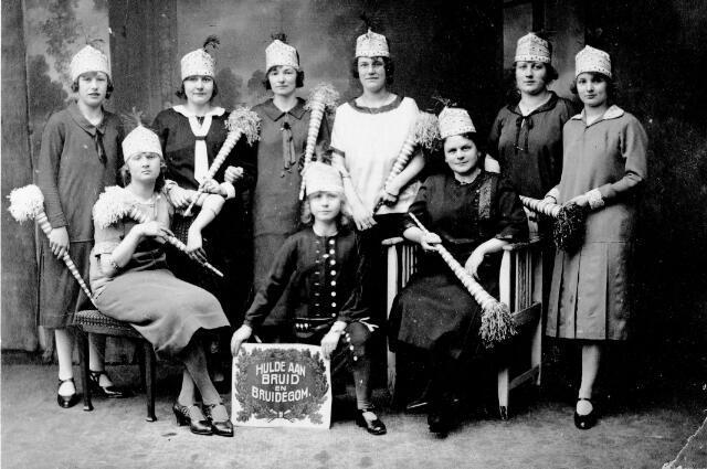 048434 - Hulde aan bruid en bruidegom. Staande derde van links Johanna Hoofs-Schoenmakers. Zij was in 1924 cheffin van de stopsters bij textielfabriek Enneking. Vermoedelijk is deze foto gemaakt ter gelegenheid van de bruiloft van een van de stopsters.