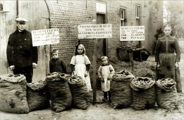 054526 - Achter de boerderij aan de Grote Voort tonen de kinderen Dirkx trots de resultaten van het gebruik van kunstmest. Van links naar rechts hun oom Peer Dirkx, Janus Dirkx, Marie Dirkx, Steef Dirkx en hun tante Koos Bruurs-van Dijck.