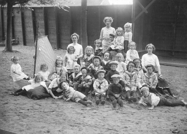 066349 - Onderwijs. Groep kleuters met kleuterleidsters. Bovenaan rechts voor de kleuterleidster, met pet, Louis Arons, geboren te Venlo op 21 november 1908, overleden te Tilburg op 5 februari 1991 als weduwnaar van Catharina van Helfteren.