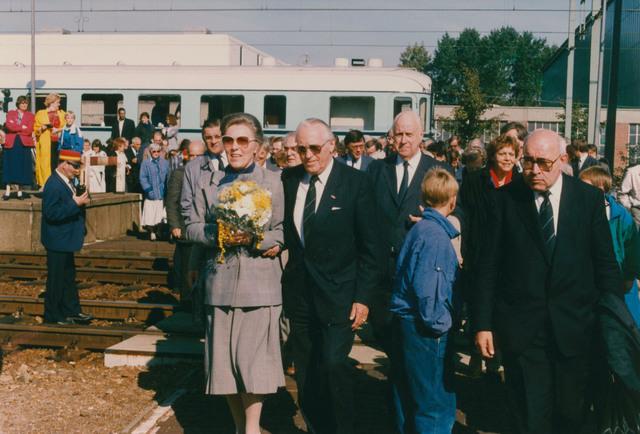 651309 - Tilburg, 125 jaar stad aan het spoor. Manifestatie. Na het welkomstwoord van de loco-burgemesster steekt het gezelschap de perronsporen over (een voetgangerstunnel is in geen velden of wegen te zien) en met aan het hoofd de heer en mevrouw Van der Harten verlaten de gasten het station.