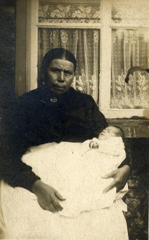 092262 - Baker Sjo van Akkerveeken met haar achternichtje Jacoba de Rooij voor de wonig aan de Akkerstraat 44 te Tilburg.  Sjo heette voluit Johanna van Akkerveeken en werd op 21 september 1854 te ´s-Hertogenbosch geboren als dochter van timmerman Jan van Akkerveeken en Adriana van Veggel. Sjo huwde op 28 september 1876 met wollenstoffenwever Petrus van Laerhoven (Tilburg 1853-1947). Sjo was baker en assisteerde bij veel bevallingen van familie en buren. Zo was zij ook aanwezig als baker bij de bevalling van Jacoba Gerardina Cornelia de Rooij op 27 juli 1915. Jacoba was een dochter van Gerdina J.M. (Dien)Cools en Johannes (Jan) H. de Rooij. De moeder van Dien Cools was een oudere zus van Sjo van Akkerveeken.