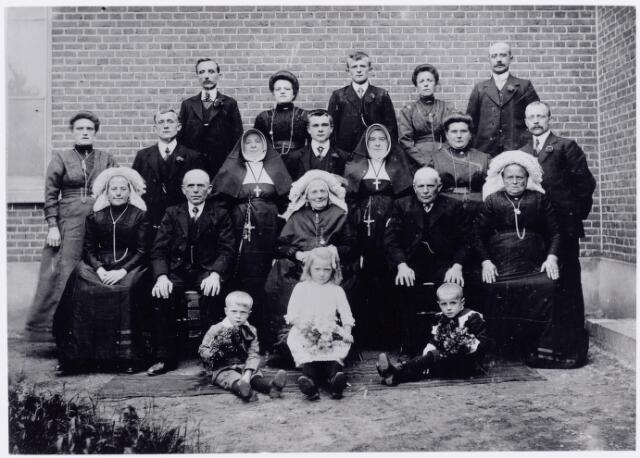 046132 - De familie Smits uit Goirle. Op de voorgrond v.l.n.r. Jan Smits Pzn. (1908-1976), Nellie de Jong, trouwde later met Toon Hoogendoorn (1909-1990) en Janus van Rooij (1908-1969). Zittend op de eerste rij v.l.n.r. Anna Catharina Maria (Trien) Smits (1872-1943), haar broer Adrianus Smits, weduwnaar van M.E. de Volder (1856-1916), zijn moeder Ida van de Ven (1831-1917) weduwe van Petrus Smits, haar zoon Jan Smits (1857-1934) en diens vrouw Johanna van den Hout (1861-1931). Staande op de volgende rij v.l.n.r. Tonnemie Venmans (1886-1970), haar man Peer Smits (1885-1969) Wilhelmina Maria (zuster Ferdinanda) Smits (1868-1941), Piet Smits Adr.zn. (1894-1965), Ida A.M. (zuster Marcelinna) Smits (1881-1959), Anna Smits (1884-1959) en haar man Frans de Jong (1883-1955). Op de laatste rij v.l.n.r. Janus Peeters (1887-1972), zijn vrouw Wilhelmina Smits (1888-1946), haar broer Michiel Smits (1893-1953), zijn zuster Drika Smits (1884-1959) en diens man Jos.H. van Rooij (1882-1949).