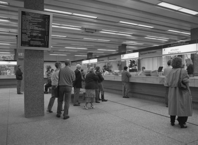 """TLB023000190_002 - Bureau Bevolking in Stadskantoor 1. Aan de diverse balies staan mensen in de rij voor o.a. aanvragen en verlenging van paspoorten en rijbewijzen. Foto gemaakt in kader van """"brochure persoonsregistratie"""""""