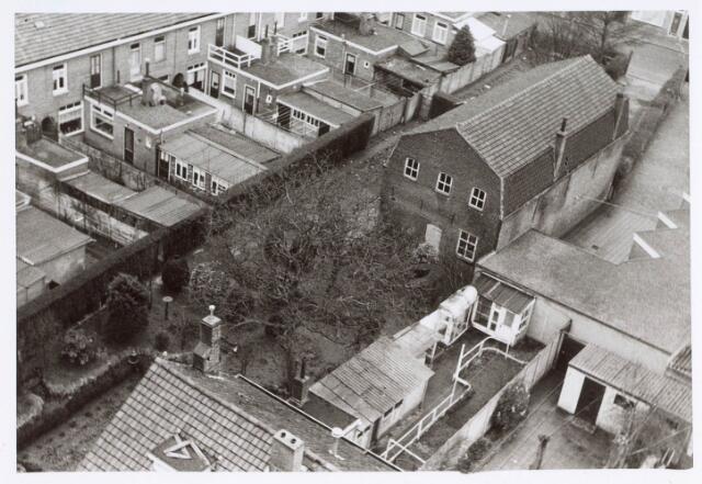 019880 - Linksboven achtergevels en tuinen van woningen aan de Bisschop van de Venstraat, onderaan daken en achtertuinen van woningen aan de Paus Adriaanstraat, rechtsboven de uitrit van de klompenmakerij Van der Pol aan de Groeseindstraat. De klompenmakerij had een zogenaamde 'franse kap.'