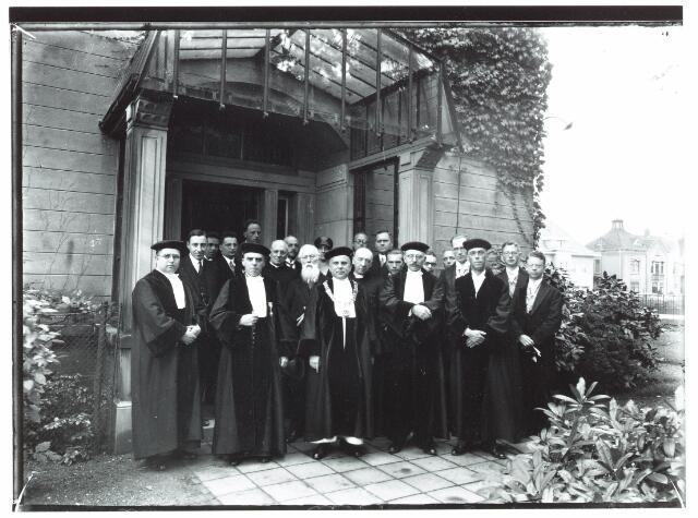 """051938 - Hoger Voortgezet Onderwijs. R.K. Handelshogeschool te Tilburg. Op deze dag vond plaats de opening van het vierde studiejaar en rectoraat overdracht. Vandaag is het vierde studiejaar van de R.K. Handels Hogeschool plechtig geopend.   Om 10.30u. droeg de heer dr. P.G.H. Dirckx, curator de plechtige H. Mis op in de St. Jozefkerk (Heuvel). Om 11.45 uur bracht de rector magnificus mgr. prof. dr. Th. Goossens verslag uit over het afgelopen studiejaar in het auditorium van het conservatorium der R.K. Leergangen. In de academische Senaat kwamen een aantal wijzigingen. Daarna werd het rectoraat overgedragen aan prof. dr. F.A. Weve o.p.. Mgr. prof. dr. Th. Goossens sprak uit het nieuwe jaar wacht voor ons. Voordat jaar mag ik het commando overgeven aan een nieuwe rector. Op uitdrukkelijk verlangen van het curatorium ben ik de drie eerste jaren het bevel daarover blijven voeren (8 oktober 1927-15 september 1930). Ik hoop het de goede koers te hebben gegeven en het langs banken en ondiepten veilig naar de wijde zee te hebben geloodst, waar het met volle zeilen zijn bestemming zal tegemoet varen. Van den heiligen Paus Petrus Celestinus die afstand deed van zijn troon om zijn stille eenzaamheid te herwinnen staat geschreven """"operi pariter et honori cessit"""". Hij deed afstand van de eer en tegelijk van het werk. Dat woord mag ik niet geheel op mijn werk toepassen. Toen het curatorium besloot naar Nederlands gebruik het rectoraat te doen wisselen droeg het mij op als beheerder toch een deel te blijven dragen van de zorg voor de opbouw van onze R.K. Handels Hogeschool. Ook die opdracht heb ik aanvaard het werk niet weigerend, wanneer men meent dat dit van nut kan zijn. Denk echter niet dr. Weve dat ik U met de rectoralen keten alleen de eer overreik. Ook van U zal onze groeiende Hogeschool wek en veel werk vragen. Doch ik weet dat gij dit gaarne zult geven en dat U niets liever is dan haar aanzien te vergroten en waardering voor haar te winnen. Moge de Heer der Wetenschappen"""