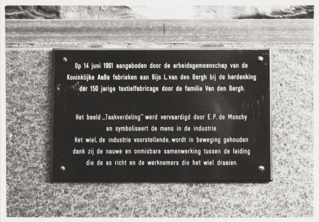 """068047 - De tekst op de sokkel van het bronzen beeld TAAKVERDELING luidt: """"Op 14 juni 1961 aangeboden door de arbeidsgemeenschap van de Koninklijke AaBe Fabrieken aan Gijs L. van den Bergh bij de herdenking der 150 jarige textielfabricage door de familie Van den Bergh. Het beeld 'Taakverdeling' werd vervaardigd door E.P. de Monchy en symboliseert de mens in de industrie. Het wiel, de industrie voorstellende, wordt in beweging gehouden dankzij de nauwe en onmisbare samenwerking tussen de leiding die de as richt en de werknemers die het wiel draaien"""". Zie ook fotonr. 068046. Trefwoorden: kunst, openbare ruimte, bedrijven, Hoevenseweg."""