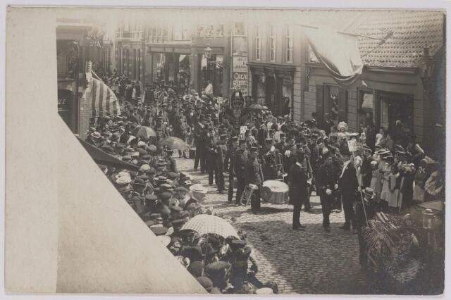 042624 - Optocht in de Heuvelstraat omstreeks 1910. Gezien de vlaggen aan de gevels zou het verband kunnen houden met de verjaardag van een lid van het Koninklijk Huis of ter gelegenheid van een tentoonstelling.