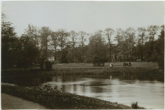 604792 - Vijver en Wilhelminaboom in het Wilhelminapark, groepje mannen op een bankje, wandelende kinderen