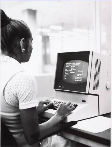 032696 - Secretaresse die op een van de twee aanwezige beeldschermen (IBM 2260) het bevolkingsbestand muteert aan de hand van vragen die door de computer op het beeldscherm worden afgebeeld in de hal van de bevolking en burgerlijke stand van het nieuw gebouwde gemeentelijk administratiegebouw aan het Stadhuisplein 130.  Op 12 oktober  1973 werd een geautomatiseerde bevolkingsadministratie met willekeurig geheugen en toepassing van teleprocessing officeel in gebruik genomen;  het systeem, dat werkt met een IBM Systeem 360 Model 40 van 128 K en zes beeldstations is een   primeur in Europa.  Vlak achter de balie  staan 3 beeldstations waarmee binnen enkele seconden de gewenste persoonsgegevens uit bevolkingsbestand zichbaar gemaakt kunnen worden. Via een hiermee verbonden schrijfmachine worden daarna deze gegevens op plakstrookjes afgedrukt.