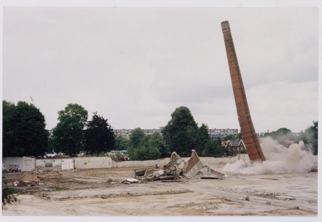 043843 - Het opblazen van de fabrieksschoorsteen op het terrein van de Regenboog aan de Bredaseweg.