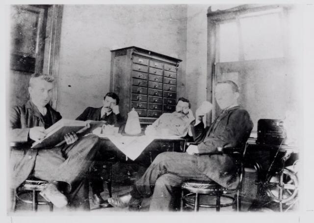 045787 - Het kantoorpersoneel van de firma Van Puijenbroek. Van links naar rechts Huub de Bont (1887-1975), Hendrik W. Janson (1878-1963), Toon Smulders (1873-1917) en Theodoor van Gils (1885-1952) Op de achtergrond een archiefkast.
